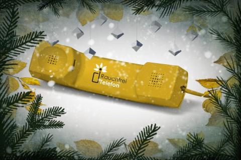 Gelber Telefonhörer mit Weihnachtsdekoration